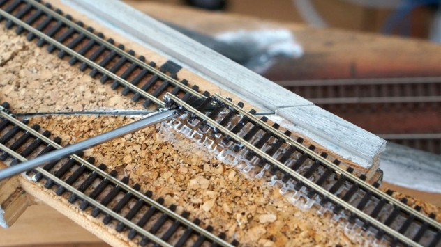 Ist der Weißleim aufgeweicht, so kann das Gleis aus seinen Klebebett gehebelt werden